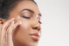 Жизнерадостный африканский заботить девушки ее кожи стоковое фото rf