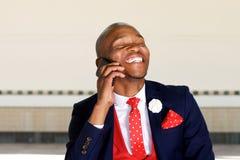Жизнерадостный африканский человек бизнесмена говоря на мобильном телефоне Стоковое Фото