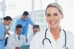 Жизнерадостный белокурый доктор представляя с коллегами в предпосылке Стоковые Фото