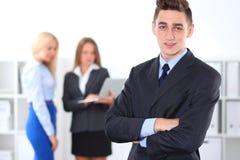 Жизнерадостный бизнесмен в офисе с коллегами на заднем плане, start-up команда стоковые изображения rf