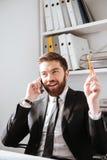 Жизнерадостный бизнесмен говоря телефоном и держа карандаш Стоковые Изображения