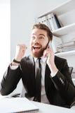 Жизнерадостный бизнесмен говоря телефоном и делает победителя показывать Стоковые Изображения