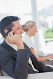 Жизнерадостный бизнесмен на телефоне при его коллега работая дальше Стоковые Изображения