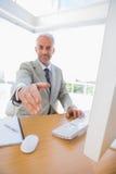 Жизнерадостный бизнесмен достигая руку вне для рукопожатия Стоковые Фотографии RF