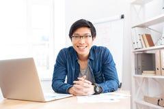 Жизнерадостный бизнесмен работая с компьтер-книжкой на рабочем месте Стоковая Фотография