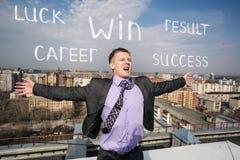 Жизнерадостный бизнесмен стоя на крыше Стоковая Фотография