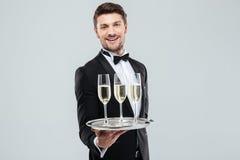 Жизнерадостный дворецкий в шампанском смокинга усмехаясь и предлагая стоковые изображения rf