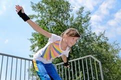 Жизнерадостный девочка-подросток катаясь на коньках в парке стоковые изображения