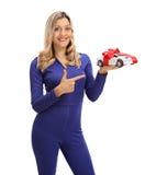 Жизнерадостный женский гонщик автомобиля держа модельный автомобиль и указывать Стоковое Изображение