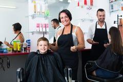 Жизнерадостный женский мальчик волос вырезывания парикмахера Стоковые Изображения