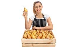 Жизнерадостный женский поставщик с клетью заполнил с грушами стоковая фотография