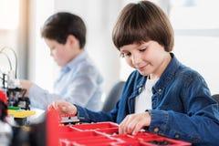 Жизнерадостный заинтересованный усмехаясь ребенок делая игрушку Стоковые Изображения