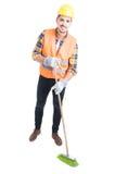 Жизнерадостный инженер подметая пол с веником Стоковые Изображения RF