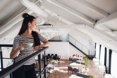 Жизнерадостный и счастливый усмехаясь кофе взятия удерживания женщины отсутствующий на ресторане Стоковое Фото