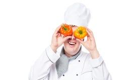 Жизнерадостный кашевар смотря в перец оба бинокля на белизне Стоковые Изображения