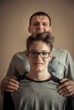 Жизнерадостный красивый мальчик подростка с отцом как портрет семьи стоковое фото
