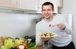 Жизнерадостный красивый человек держа плиту с салатом Стоковая Фотография