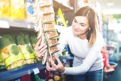 Жизнерадостный клиент девушки ища вкусные закуски в супермаркете Стоковое Изображение RF