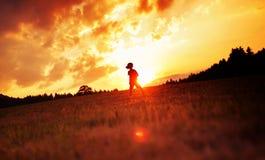 Жизнерадостный мальчик играя футбол на луге стоковое фото rf