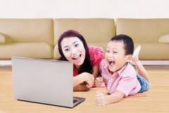 Жизнерадостный мальчик и его мать используя компьтер-книжку Стоковая Фотография