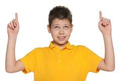 Жизнерадостный мальчик показывая его перста вверх Стоковое Изображение