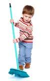 Жизнерадостный мальчик подметая пол с a Стоковые Фотографии RF