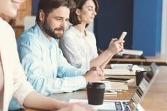 Жизнерадостный моложавый парень с бородой и женщины работая в офисе Стоковые Изображения RF