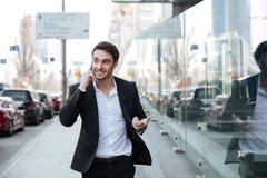 Жизнерадостный молодой бизнесмен говоря телефоном около делового центра Стоковые Фото