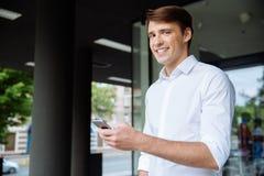 Жизнерадостный молодой бизнесмен используя smarphone и усмехаться около делового центра Стоковая Фотография