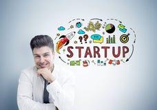 Жизнерадостный молодой бизнесмен около startup серой стены Стоковая Фотография