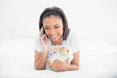 Жизнерадостный молодой темный с волосами модельный делая телефонный звонок пока прижимающся овца плюша Стоковое Изображение