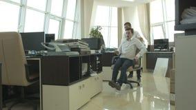 Жизнерадостный молодой человек 2 ехать стул в офисе видеоматериал