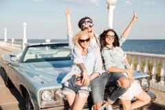 Жизнерадостный молодой человек и 2 женщины стоя с поднятыми руками Стоковые Фото