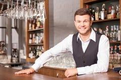 Жизнерадостный мужской бармен работает в пабе стоковые фото