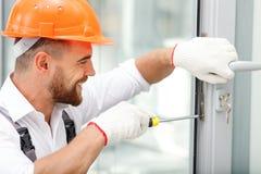 Жизнерадостный мужской ремонтник работает с утехой Стоковые Фото