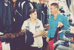 Жизнерадостный мужчина и его покупки сына резвятся одежда Стоковое фото RF