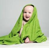 Жизнерадостный младенец в зеленом полотенце на предпосылке Стоковое Изображение RF