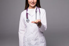 Жизнерадостный доктор молодой женщины при стетоскоп показывая пилюльку в ее руке изолированной на сером цвете Стоковые Изображения
