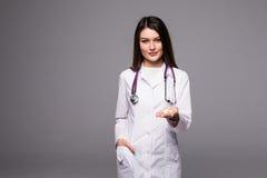 Жизнерадостный доктор молодой женщины при стетоскоп показывая пилюльку в ее руке изолированной на сером цвете Стоковое Фото