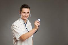 Жизнерадостный доктор представляя с стетоскопом Стоковые Фото
