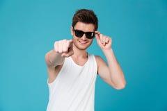 Жизнерадостный парень в солнечных очках и синглете указывая палец на камеру стоковые фотографии rf