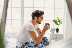 Жизнерадостный парень наслаждаясь горячим питьем на кровати Стоковое Фото