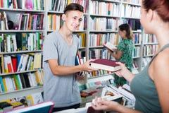 Жизнерадостный подросток мальчика принимая новую книгу от продавца стоковое изображение rf