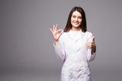 Жизнерадостный привлекательный доктор молодой женщины держа пилюльку и показывая большие пальцы руки вверх над серой предпосылкой Стоковые Фотографии RF