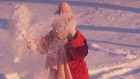 Жизнерадостный ребенок играя в снеге видеоматериал