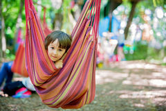 Жизнерадостный ребенок играя и лежа внутри гамака Стоковое Фото