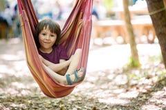 Жизнерадостный ребенок играя и лежа внутри гамака Стоковые Изображения