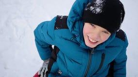 Жизнерадостный ребенок идет и усмехается snowtube на снежных дорогах видеоматериал