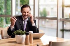 Жизнерадостный усмехаясь человек говоря на сотовом телефоне Стоковые Фотографии RF