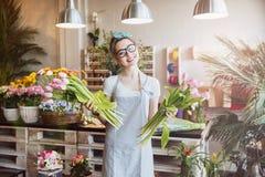Жизнерадостный флорист женщины держа 2 пука розовых тюльпанов Стоковое Фото